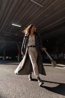 Vrolijk mooi lachend meisje met krullende haren in een modieuze lange jas met een trui, broek, laarzen en een stijlvolle handtas loopt op een zonnige dag door de stad. stedelijke vrouwelijke stijl en vrolijke schoonheid