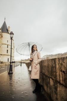 Vrolijk mooi meisje dat transparante paraplu houdt die buiten slentert.