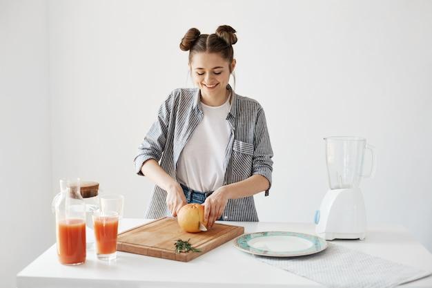 Vrolijk mooi meisje die scherpe grapefruit voor ontbijt over witte muur glimlachen. gezonde detox-smoothie. fitness eten.