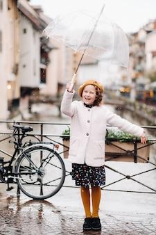 Vrolijk mooi meisje in een jas met een doorzichtige paraplu in annecy