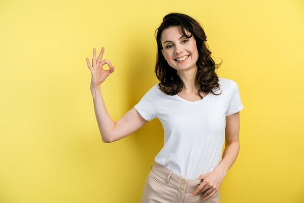 Vrolijk, mooi meisje met donker haar in een t-shirt toont ok gebaar