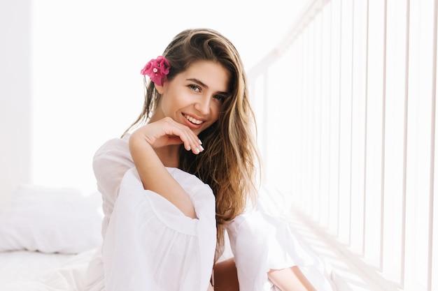 Vrolijk mooi meisje met geweldige glimlach en romantisch kapsel poseren graag in witte kamer. portret van schattige jonge vrouw met roze bloem in haar, zittend op bed in zonnige ochtend en lachen