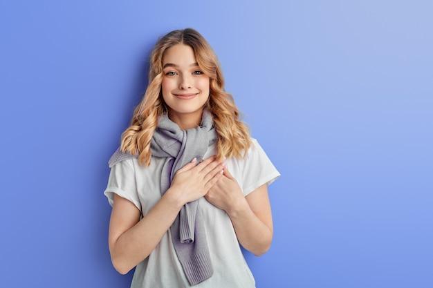 Vrolijk mooi meisje met handen op de borst dankbaarheid voelen