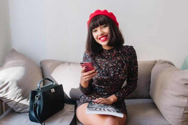 Vrolijk mooi meisje met trendy kapsel iphone houden en lezen van nieuwe berichten zittend op grijze coach. portret van schattige jonge vrouw in franse baret en retro kleding met telefoon en tijdschrift