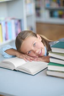 Vrolijk mooi schoolmeisje dat op een bibliotheekboek ligt