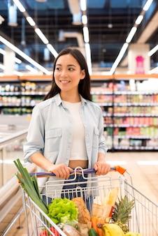 Vrolijk mooi wijfje met boodschappenwagentje bij supermarkt
