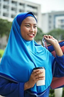 Vrolijk moslimvrouwtje met warme drank na het winkelen