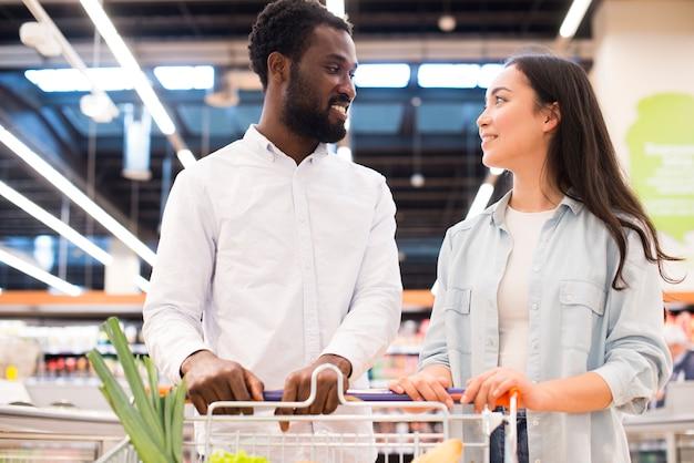 Vrolijk multi-etnisch paar met boodschappenwagentje bij supermarkt
