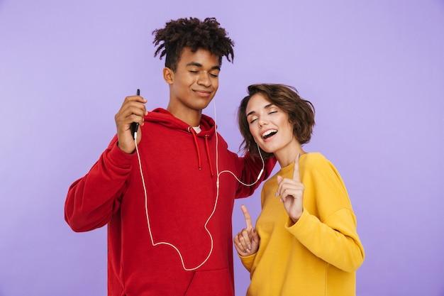 Vrolijk multi-etnisch tienerpaar staan samen geïsoleerd, luisteren naar muziek met oortelefoons, met mobiele telefoon