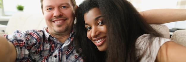 Vrolijk multi-etnisch verliefd stel zit in omhelzing in een gezellige woonkamer thuis