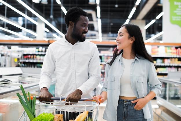 Vrolijk multiraciaal paar met boodschappenwagentje bij supermarkt