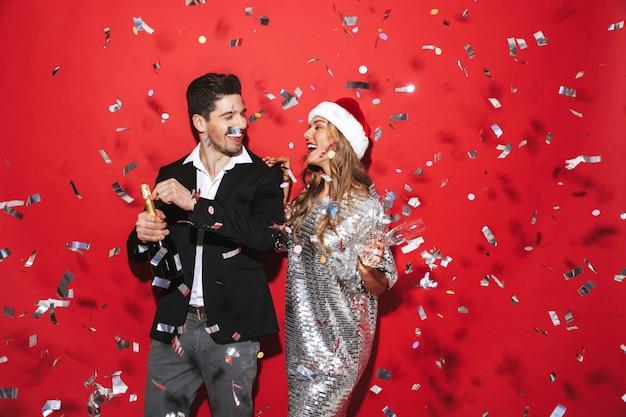 Vrolijk netjes gekleed paar staande geïsoleerd over rode ruimte, nieuwjaar vieren
