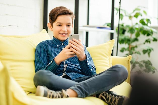 Vrolijk ontspannen schooljongens zittend op de bank met zijn benen gekruist en lachend terwijl hij naar het scherm van de moderne smartphone in zijn handen keek
