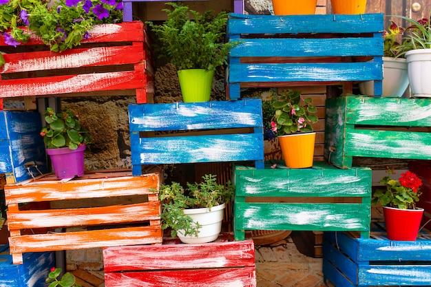Vrolijk ontwerp van veelkleurige houten kisten en bloempotten.