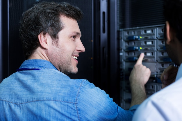 Vrolijk opgetogen aardige man wijzend op het serverrek en lacht terwijl hij naar zijn collega keek