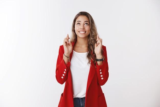 Vrolijk opgewonden charmant optimistisch schattig vrouwtje met rode jas biddend kijkende luchten kruis vingers veel geluk anticiperend op goed nieuws breed glimlachen hopelijk dromen wens komt uit