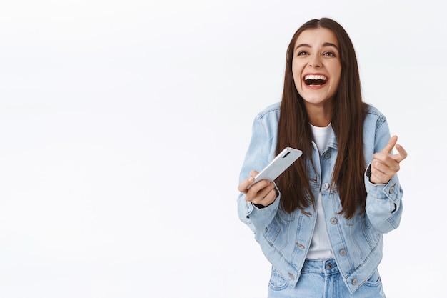 Vrolijk, opgewonden, opgelucht aantrekkelijk meisje in spijkerjasje, smartphone horizontaal houden, glimlachend en tevreden lachen, moeilijk spelniveau halen, overwinning vieren, winnen voelt als kampioen