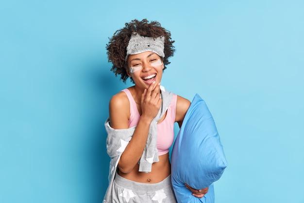Vrolijk oprecht etnisch krullend meisje in nachtkleding glimlacht in grote lijnen bereidt zich voor op slaap houdt kussen heeft goed humeur geïsoleerd op blauwe achtergrond ondergaat schoonheidsbehandelingen.