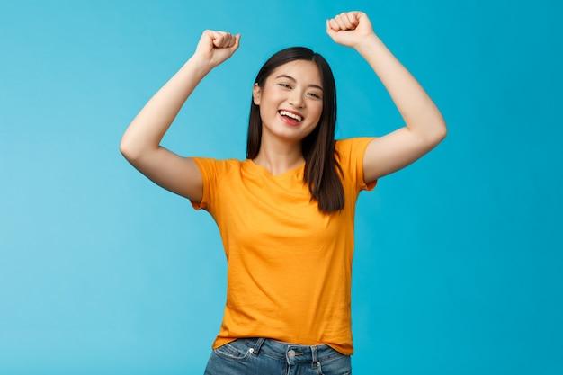 Vrolijk, optimistisch, schattig aziatisch meisje steekt handen vuistpomp op, viert de overwinning, juicht voor het favoriete team, lacht breed steunt vriend scoorde doelpunt, behaalt succes, triomfeert.