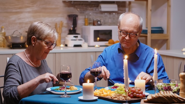 Vrolijk oud gepensioneerd verliefd stel dat thuis eet. ouder paar eten en discussiëren tijdens een romantisch diner zittend aan tafel in de moderne keuken, samen genietend van tijd