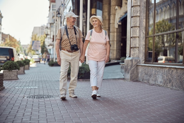 Vrolijk oud toeristenpaar dat hand in hand door het stadscentrum loopt