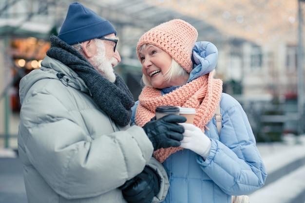 Vrolijk ouder echtpaar in winterkleren dat buiten staat met kartonnen kopjes warme drank en vriendelijk naar elkaar kijkt en glimlacht