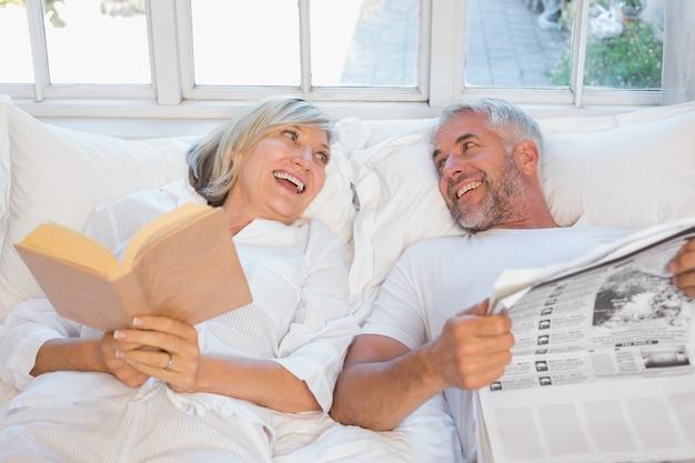 Vrolijk ouder echtpaar met krant en boek in bed