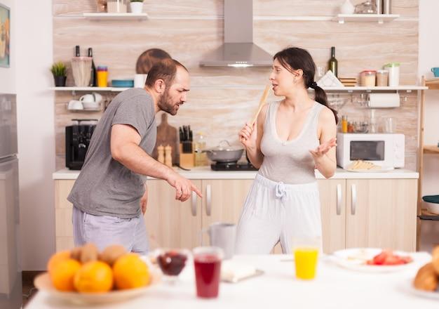 Vrolijk paar dansen in de keuken en plezier hebben tijdens het ontbijt. zorgeloze man en vrouw lachen, zingen, dansen luisteren mijmerend, gelukkig en zorgeloos leven. positieve mensen