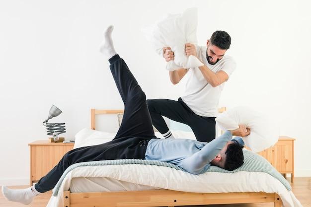 Vrolijk paar dat pret met hoofdkussen op bed in de slaapkamer heeft