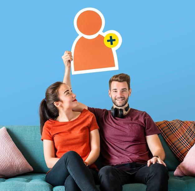 Vrolijk paar die een pictogram van het vriendenverzoek houden