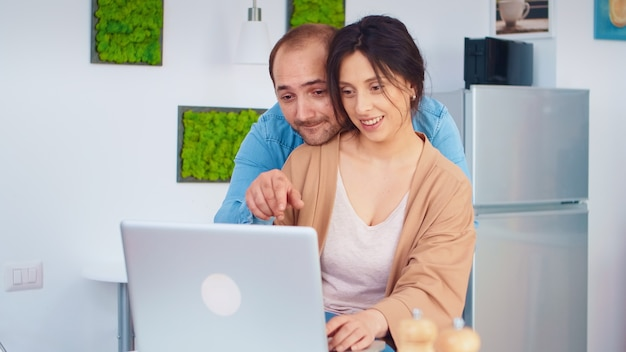Vrolijk paar die laptop in keuken gebruiken die online recept voor ontbijt lezen. man en vrouw koken recept eten. gelukkig gezond samen levensstijl. familie op zoek naar online maaltijd. gezondheid verse salade