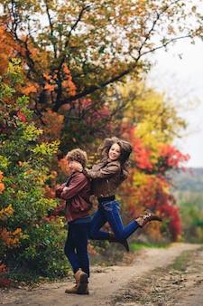 Vrolijk paar dwazen rond en toont emoties man en vrouw in leren jassen en spijkerbroeken tegen herfst bomen