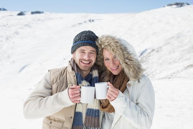 Vrolijk paar in warme kleding met koffiekoppen op gesneeuwd landschap