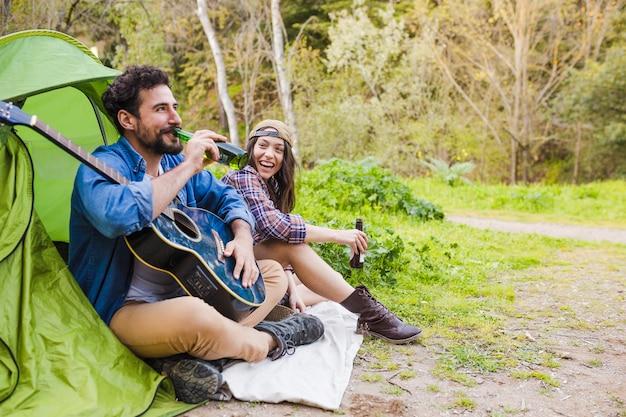 Vrolijk paar met gitaar bier drinken