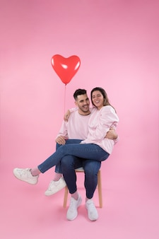 Vrolijk paar met hartballon die op stoel koestert