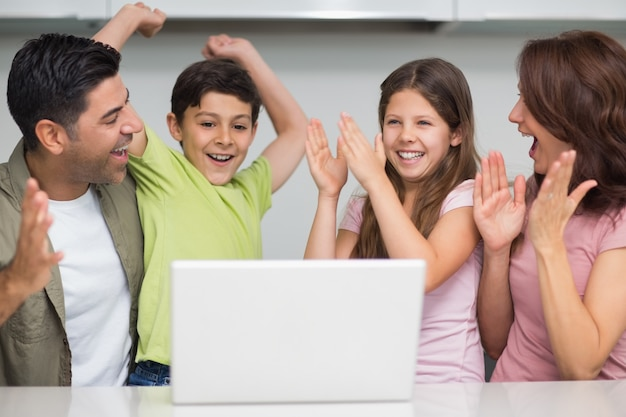Vrolijk paar met jonge geitjes die laptop met behulp van
