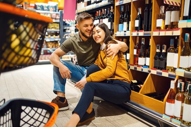 Vrolijk paar met kar in kruidenierswinkelsupermarkt samen