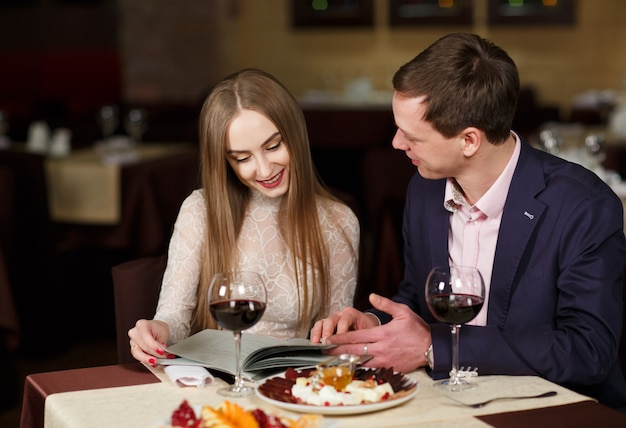 Vrolijk paar met menu in een restaurant.