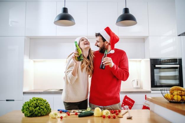 Vrolijk paar met santahoeden op bier houden en hoofden die terwijl status in keuken koesteren