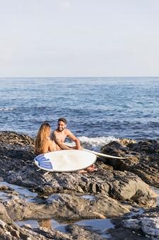 Vrolijk paar met surfplanken die op ruwe kust zitten