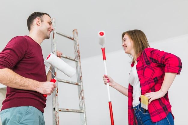 Vrolijk paar met verfrollen en ladder