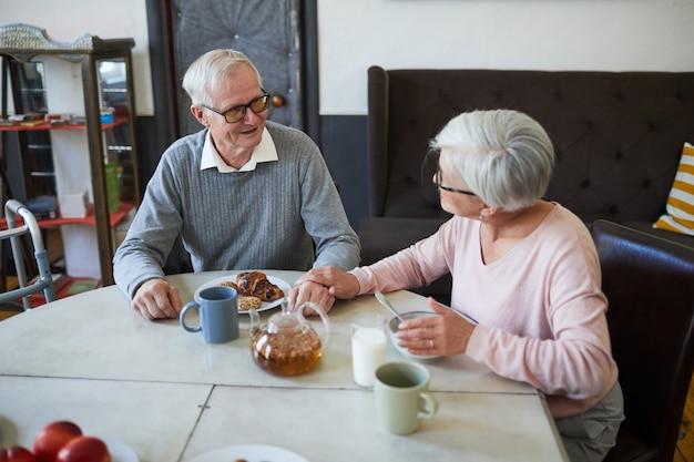 Vrolijk paar senioren die genieten van het ontbijt aan de eettafel in de kopieerruimte van het verpleeghuis