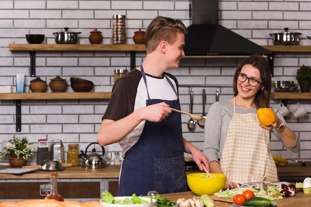 Vrolijk paar tijdens saladevoorbereiding
