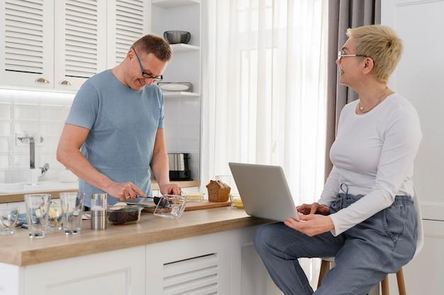 Vrolijk paar van middelbare leeftijd praten over de keuken tijdens het koken en werken op laptop