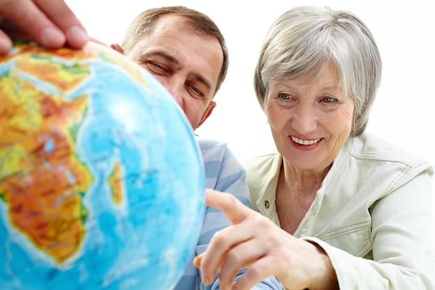 Vrolijk paar wijzend op globe