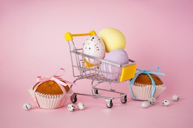 Vrolijk pasen-concept. pasen-cake en paaseieren in een kar met bloemen op een roze achtergrond.