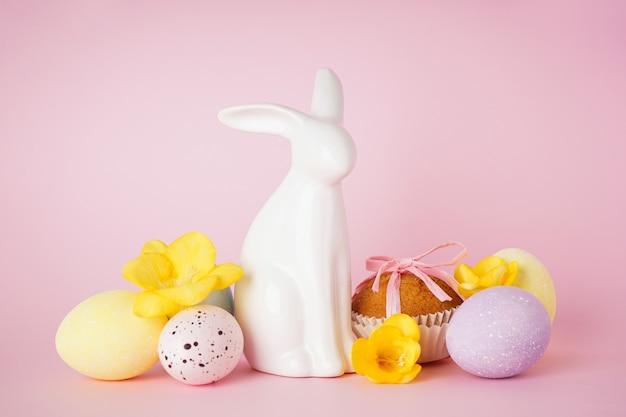 Vrolijk pasen-concept. pasen-cake, paashaas en eieren met bloemen op een roze achtergrond.
