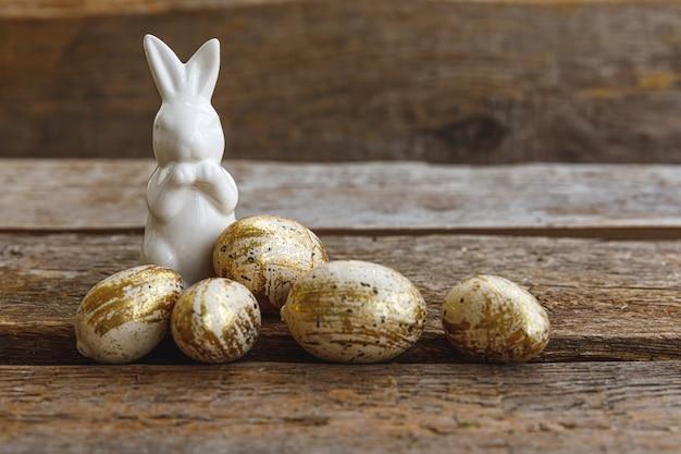 Vrolijk pasen-concept. voorbereiding op vakantie. gouden verfraaid paaseieren en konijntjesstuk speelgoed op houten achtergrond