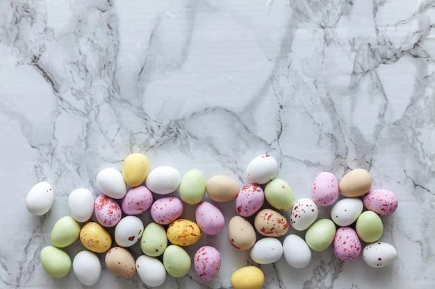 Vrolijk pasen concept. voorbereiding op vakantie. pasen pastel snoep chocolade eieren snoep op trendy grijs marmer. eenvoudig minimalisme plat lag bovenaanzicht kopie ruimte.