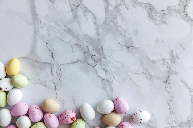 Vrolijk pasen concept. voorbereiding op vakantie. pasen pastel snoep chocolade eieren snoep op trendy grijze marmeren achtergrond. eenvoudig minimalisme plat lag bovenaanzicht kopie ruimte.